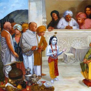 Young Krishna is propiciating his father Nanda Maharaja