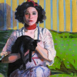 A young lady wearing a red bow is holding a cat. She is sitting on a green couch