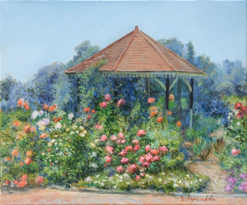 A gazebo with rose bushes in front climbing all around it.